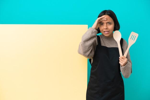 Młoda kobieta kucharz rasy mieszanej z dużą tabliczką na białym tle na niebieskim tle, patrząc daleko ręką, aby wyglądać coś