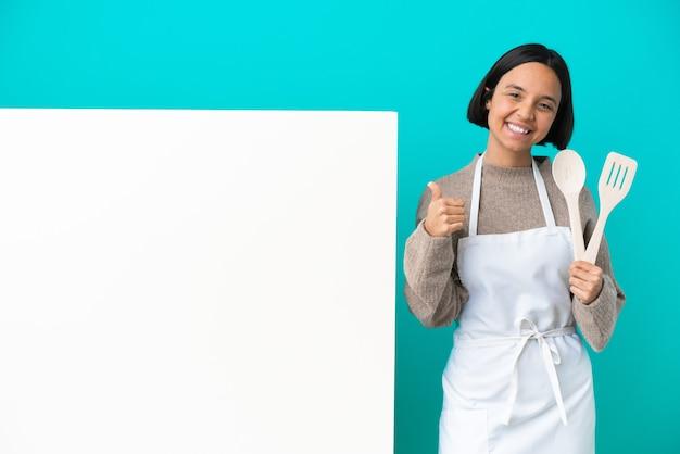Młoda kobieta kucharz rasy mieszanej z dużą tabliczką na białym tle na niebieskim tle pokazującą znak ok i gest kciuka w górę