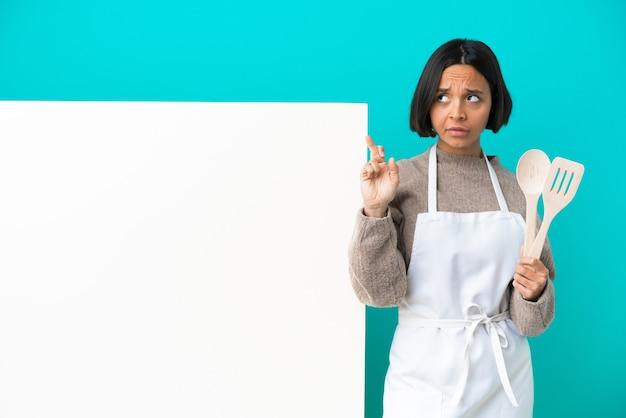 Młoda kobieta kucharz rasy mieszanej z dużą tabliczką na białym tle na niebieskim tle z palcami krzyżującymi się i życzącymi wszystkiego najlepszego
