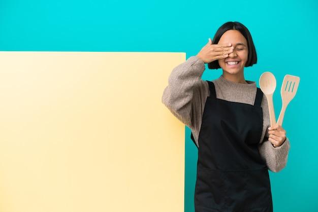 Młoda kobieta kucharz rasy mieszanej z dużą tabliczką na białym tle na niebieskim tle zakrywającą oczy rękami i uśmiechniętą