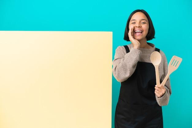 Młoda kobieta kucharz rasy mieszanej z dużą tabliczką odizolowaną na niebieskim tle krzyczącą z szeroko otwartymi ustami