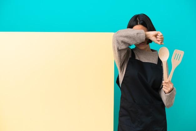 Młoda kobieta kucharz rasy mieszanej z dużą tabliczką odizolowaną na niebieskim tle zakrywającą oczy rękami