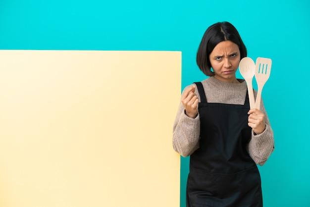 Młoda kobieta kucharz rasy mieszanej z dużym plakatem na białym tle na niebieskim tle dokonywania gest pieniędzy, ale jest zrujnowany