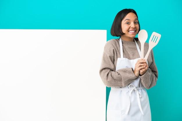 Młoda kobieta kucharz rasy mieszanej z dużym plakatem na białym tle na niebieskim tle trzyma dłoń razem. osoba o coś prosi