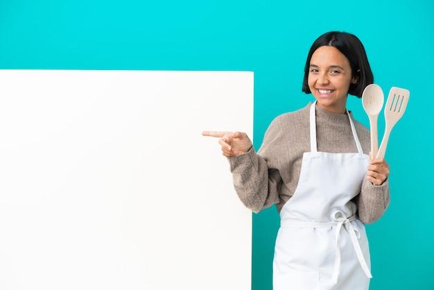 Młoda kobieta kucharz rasy mieszanej z dużym plakatem na białym tle na niebieskim tle, wskazując palcem po bokach i szczęśliwa