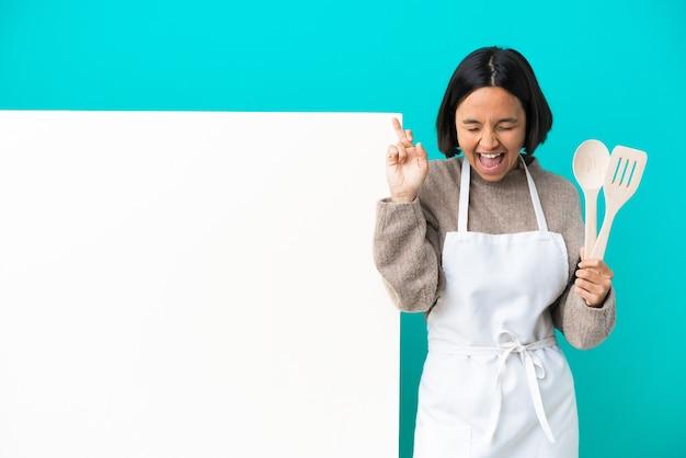 Młoda kobieta kucharz rasy mieszanej z dużym plakatem na białym tle na niebieskim tle z skrzyżowanymi palcami