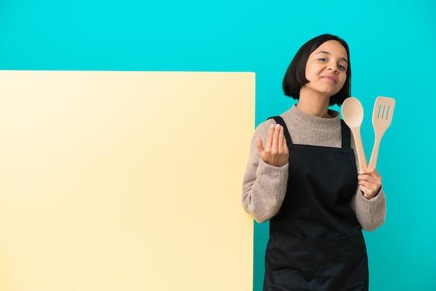 Młoda kobieta kucharz rasy mieszanej z dużym plakatem na białym tle na niebieskim tle, zapraszając do ręki. cieszę się, że przyszedłeś