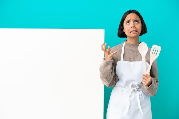 Młoda kobieta kucharz rasy mieszanej z dużym plakatem na białym tle zestresowana przytłoczona