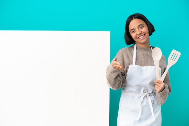 Młoda kobieta kucharz rasy mieszanej z dużym plakatem odizolowanym na niebieskiej ścianie wyciągając ręce na bok, by zaprosić do przyjścia