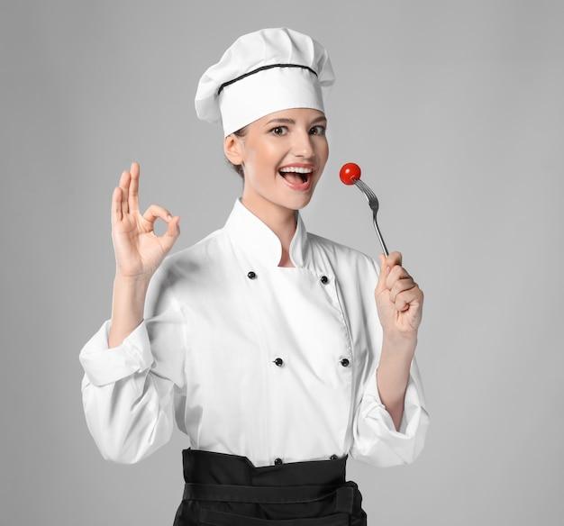 Młoda kobieta kucharz robi ok gest