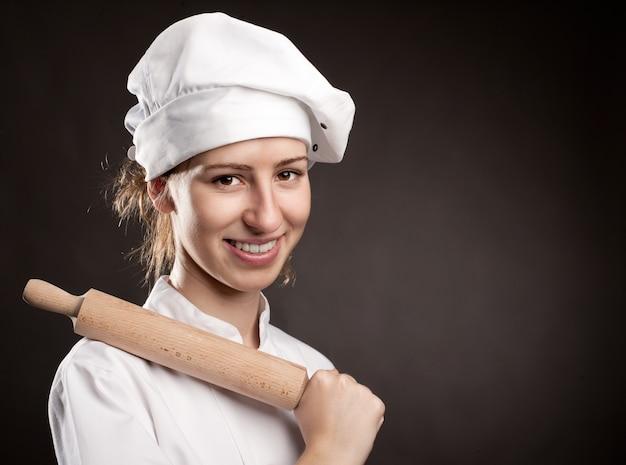 Młoda kobieta kucharz trzyma wałek do ciasta