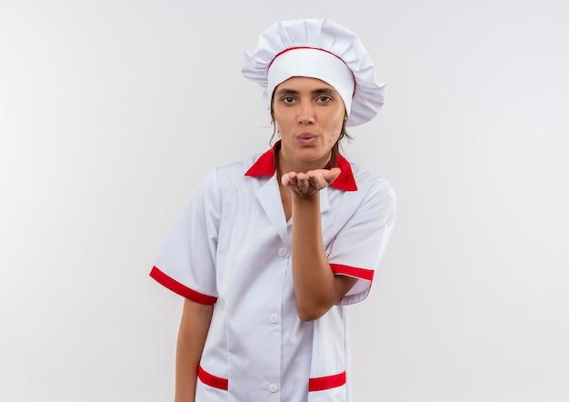 Młoda kobieta kucharz ubrana w mundur szefa kuchni pokazujący gest pocałunku na odosobnionej białej ścianie z miejsca na kopię
