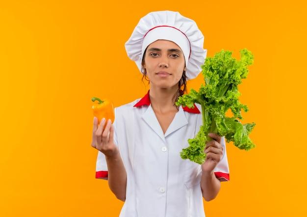 Młoda kobieta kucharz ubrana w mundur szefa kuchni trzymając sałatkę i pieprz na odizolowanych żółtej ścianie z miejsca na kopię