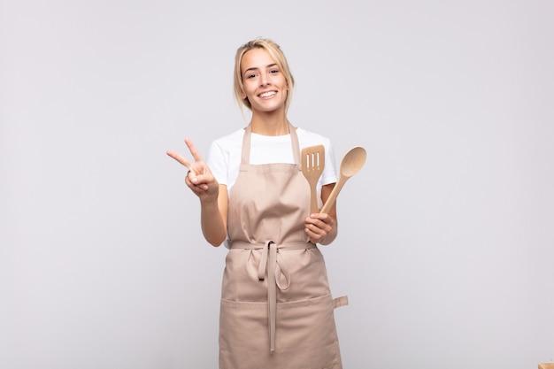 Młoda kobieta kucharz uśmiecha się i wygląda przyjaźnie, pokazując numer dwa lub sekundę z ręką do przodu, odliczając
