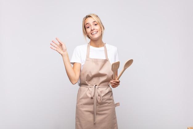 Młoda kobieta kucharz uśmiecha się radośnie i wesoło, macha ręką, wita i wita lub żegna się