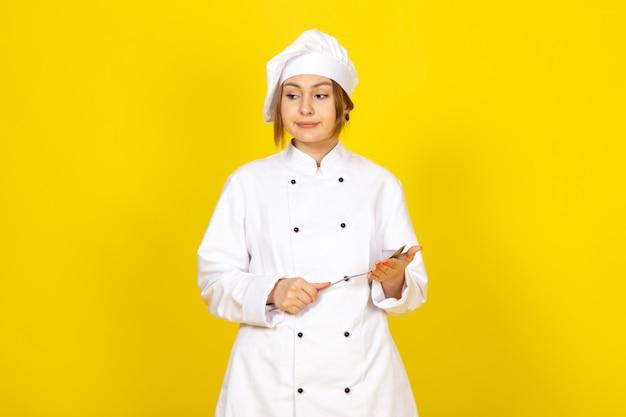 Młoda kobieta kucharz w białym garniturze i białej czapce pozowanie, myśląc, trzymając srebrną łyżkę niezadowolony