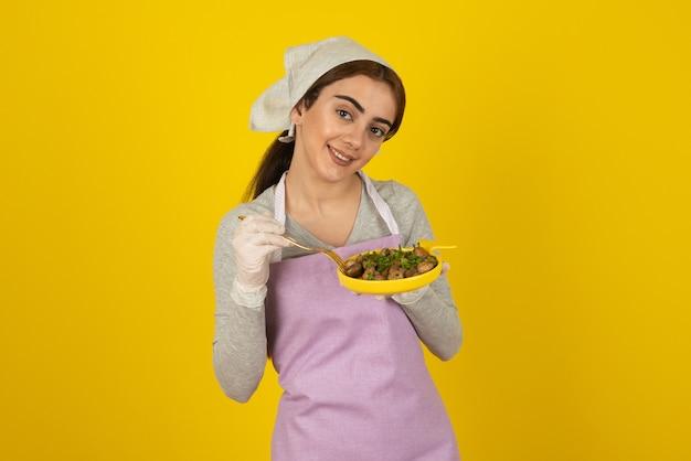 Młoda kobieta kucharz w fartuch jedzenie smażonych grzybów na żółtej ścianie.