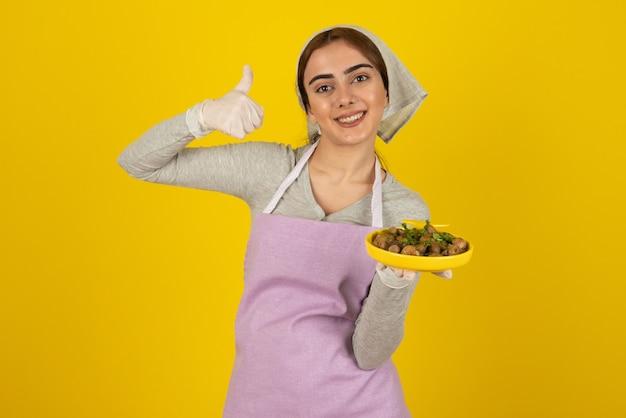 Młoda kobieta kucharz w fartuch, trzymając talerz smażonych grzybów i pokazując kciuk do góry.