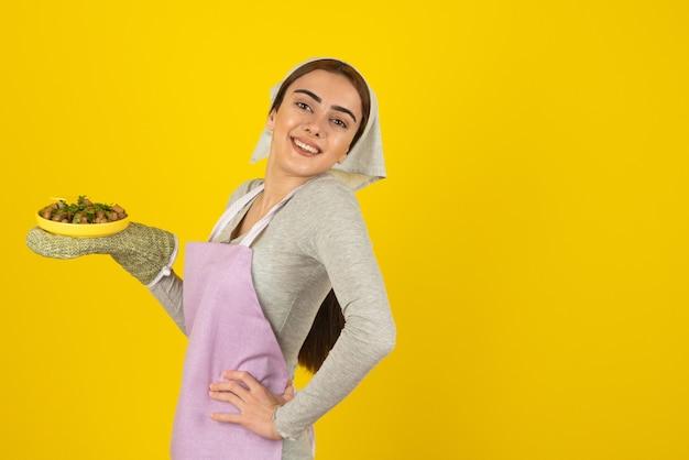 Młoda kobieta kucharz w fioletowy fartuch pozowanie z talerzem smażonych grzybów na żółtej ścianie.