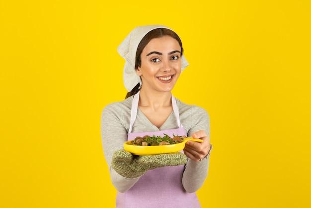 Młoda kobieta kucharz w fioletowy fartuch utrzymując talerz smażonych grzybów na żółtej ścianie.