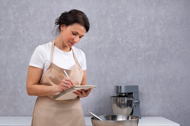 Młoda kobieta kucharz w kuchni pisze przepis w książce kucharskiej. portret gospodyni.