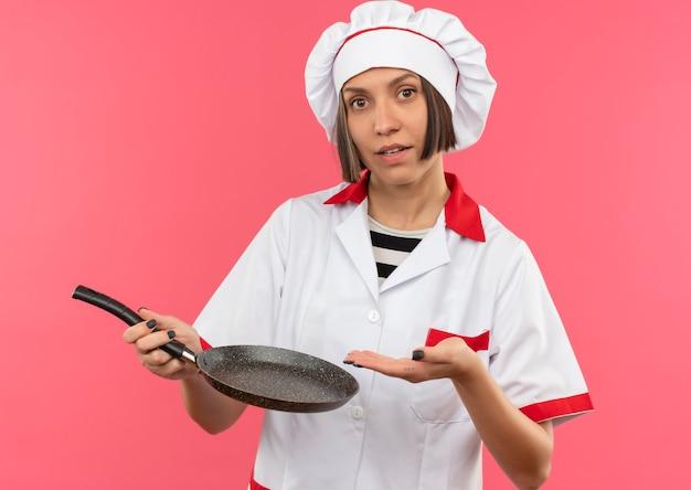 Młoda kobieta kucharz w mundurze szefa kuchni, trzymając i wskazując ręką na patelni patrząc na kamery na białym tle na różowym tle