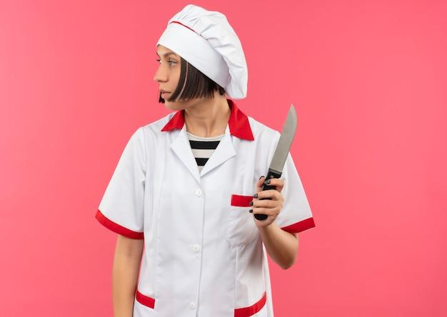 Młoda kobieta kucharz w mundurze szefa kuchni trzymając nóż i patrząc na bok na białym tle na różowym tle z miejsca na kopię