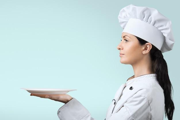 Młoda kobieta kucharz z pustym talerzem na niebieskim tle