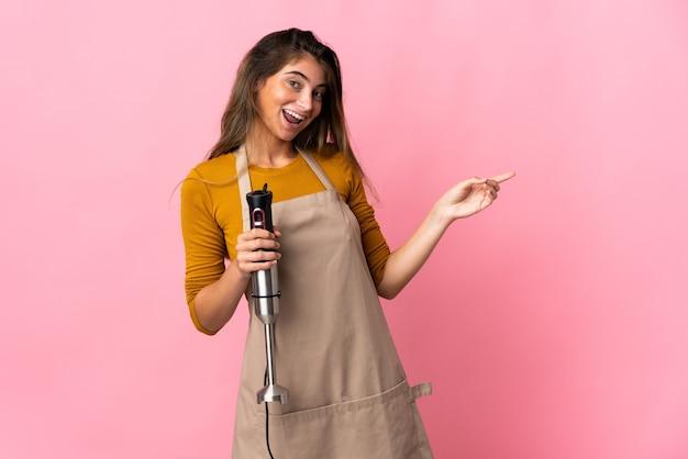 Młoda kobieta kucharz za pomocą ręcznego blendera na białym tle na różowej ścianie wskazując palcem na bok i prezentuje produkt