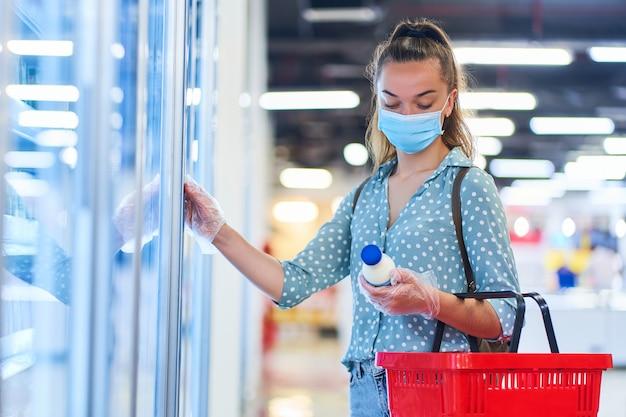 Młoda kobieta kupująca w ochronnej masce i przezroczystych rękawiczkach z koszykiem wybiera produkty mleczne z zamrażarki w centrum handlowym