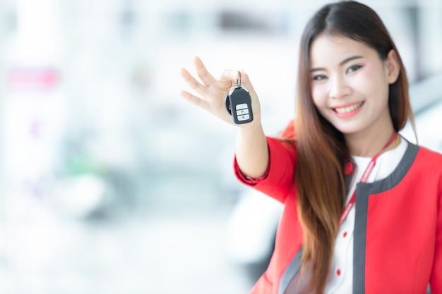 Młoda kobieta kupuje samochód odbierając klucze swojego nowego samochodu,