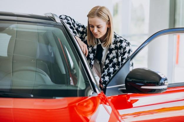 Młoda kobieta kupuje samochód w samochodowej sala wystawowej
