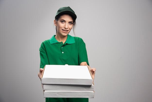 Młoda kobieta kurier rozdaje pudełka po pizzy na szarym tle.