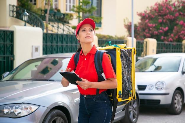Młoda kobieta kurier szuka domu i trzyma tablet. zamyślona dostawczyni w czerwonej czapce i koszuli, niosąca z zamówieniem żółtą termo torebkę. dostawa i koncepcja zakupów online