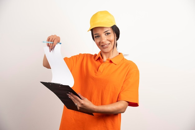 Młoda kobieta kurier trzymając schowek na białej ścianie.
