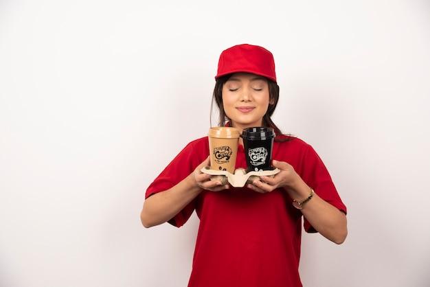 Młoda kobieta kurier wącha aromat kawy do dostawy na białym tle
