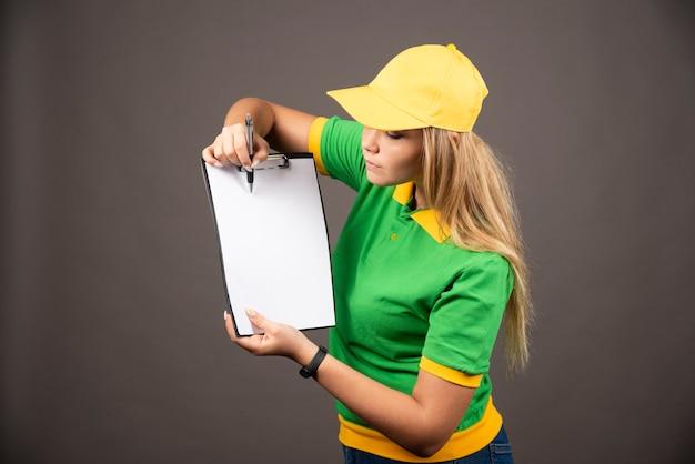 Młoda kobieta kurier z ołówkiem patrząc na schowka.