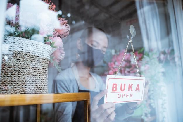Młoda kobieta kwiaciarni ubrana w fartuch i maskę na twarz stojąca przy oknie wiaderka z kwiatami, dając otwarty znak tekstowy w oknie