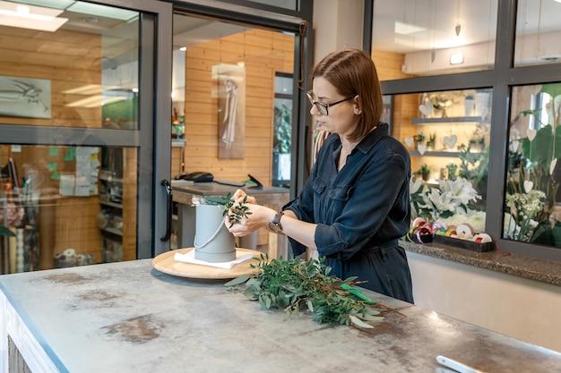 Młoda kobieta kwiaciarnia w okularach i ubraniach casual, zbiera bukiet kwiatów z zieleni. warsztaty kwiatowe, koncepcja małych firm.
