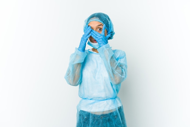 Młoda kobieta łacińskiej chirurg na białym tle mruga przez palce przestraszona i zdenerwowana.