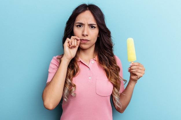 Młoda kobieta łacińskiej gospodarstwa lody na białym tle na niebieskim tle z palcami na ustach zachowując tajemnicę.