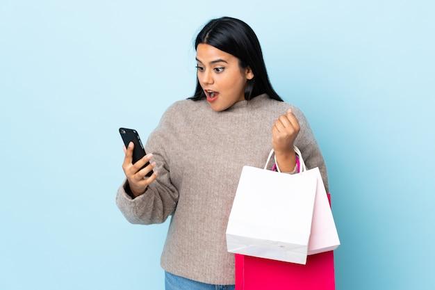 Młoda kobieta łacińskiej kobieta na niebieską ścianą gospodarstwa torby na zakupy i pisanie wiadomości z jej telefonu komórkowego do przyjaciela