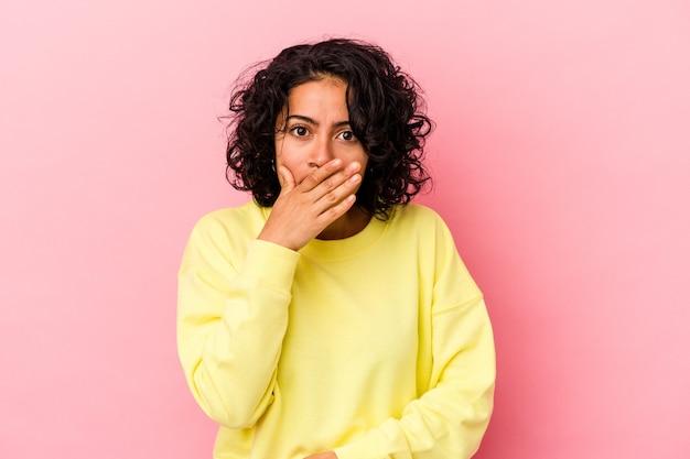 Młoda kobieta łacińskiej kręcone na białym tle na różowym tle obejmujące usta rękami patrząc zmartwiony.