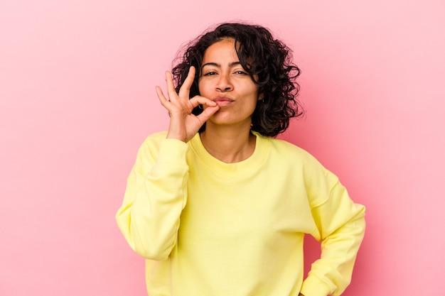 Młoda kobieta łacińskiej kręcone na białym tle na różowym tle z palcami na ustach zachowując tajemnicę.