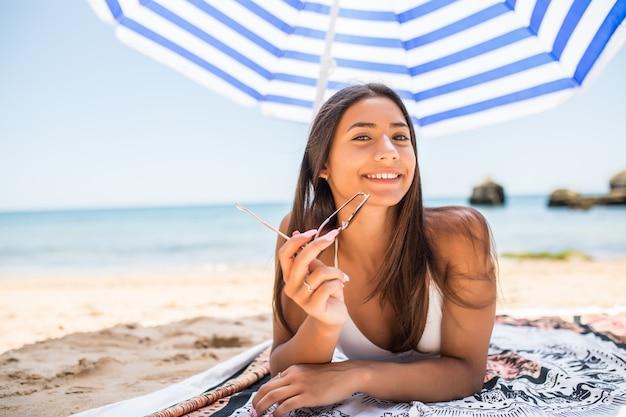 Młoda kobieta łacińskiej, leżąc na piasku pod parasolem na plaży. letnie powołanie