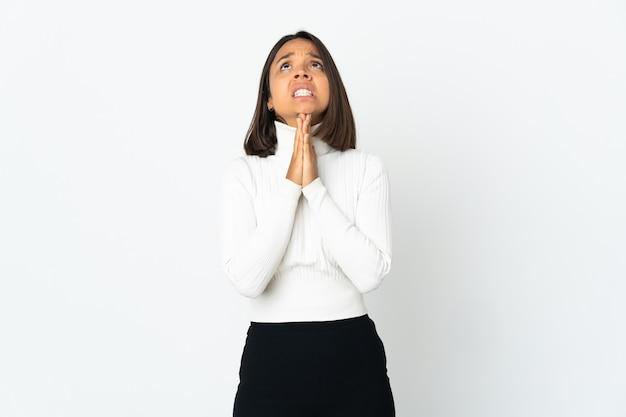 Młoda kobieta łacińskiej na białym tle na białej ścianie trzyma dłoń razem. osoba o coś prosi