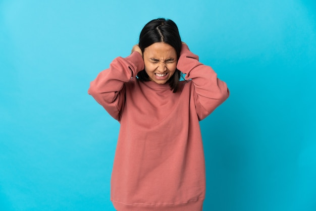 Młoda kobieta łacińskiej na białym tle na niebieskim tle sfrustrowani i zakrywający uszy