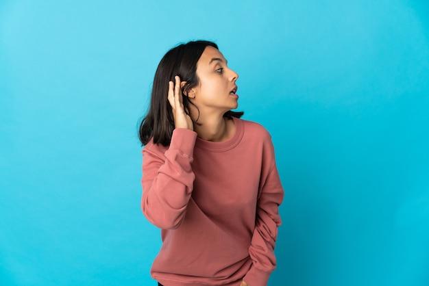 Młoda kobieta łacińskiej na białym tle na niebieskim tle, słuchając czegoś, kładąc rękę na uchu