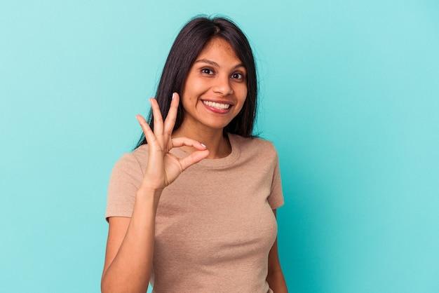 Młoda kobieta łacińskiej na białym tle na niebieskim tle wesoły i pewny siebie, pokazując ok gest.