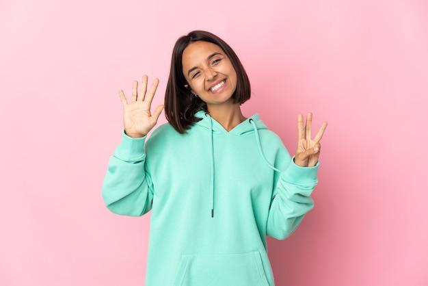 Młoda kobieta łacińskiej na białym tle na różowym tle, licząc osiem palcami
